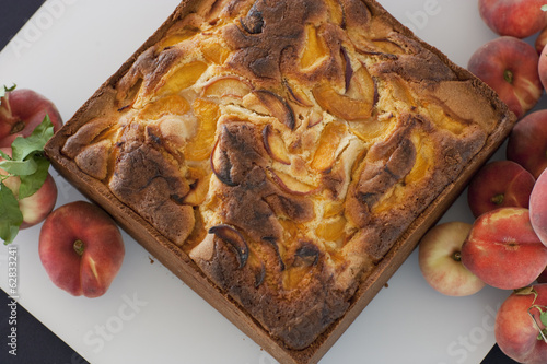 A square baked peach cake on a board with fresh peaches. Fruits. Organic fresh food on a farm stand.