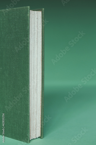 A hard cover book with a green cover, and white paper page edges, upright on a green background.