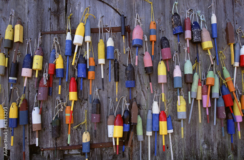 Fishing marker marine buoys or floats hanging on a fishing shed wall on the waterfront.