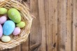 canvas print picture - Easter eggs in nest on color wooden background