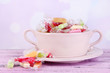 Tasty candies in bowl on table on bright background