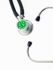 A doctor's stethoscope, a diagnostic instrument for assessment of health. Black tubing. Ear pieces, and a chest piece containing green pills.