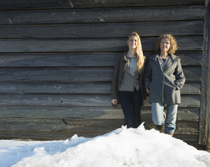 A mother and daughter standing leaning against the wooden wall of a barn on a farm. Snow piled up at their feet.