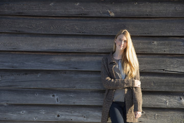 A young woman leaning against the wooden wall of a barn wearing a long knitted coat.