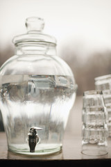 Drinking water in a large clear glass container. A stack of glasses. Pure chilled water.