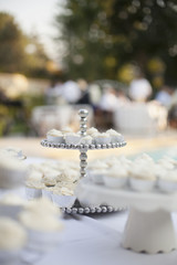 A table laid for a banquet or a wedding breakfast. White table cloth, cake stand, and table setting.