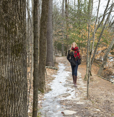 A woman in a winter coat and red scarf walking down a woodland path, in winter.