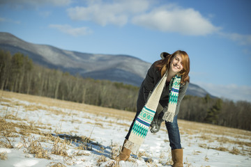 A young woman in a snowy field in a rural landscape. Scooping up snow to make a snowball.