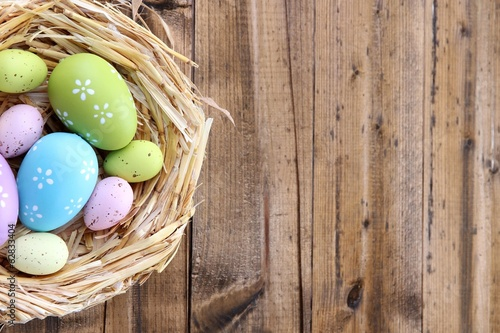 Foto op Plexiglas Egg Easter eggs in nest on color wooden background