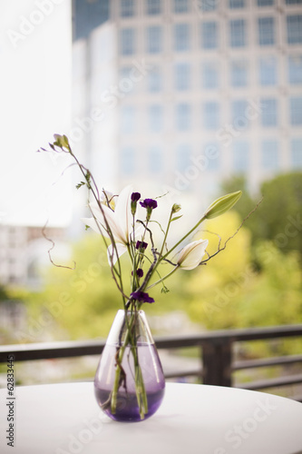 A table on a terrace in the city. A vase of flowers. Small purple flowers, and white lily and orchid blooms.