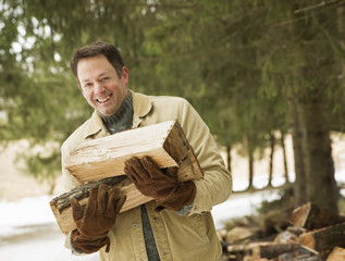 A man outdoors carrying an armful of logs