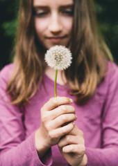 A ten year old girl holding a dandelion clock seedhead on a long stem.