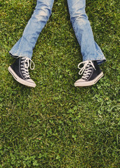 A ten year old girl lying on the grass. Cropped view of her lower legs. Wearing sneakers and faded blue jeans.