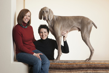 A same sex couple, two women posing with their Weimaraner pedigree dog.