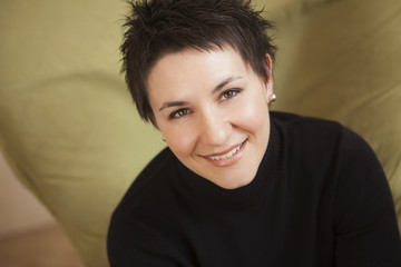 A woman with short spiky brown hair, wearing a black turtleneck sweater. Smiling and looking up.