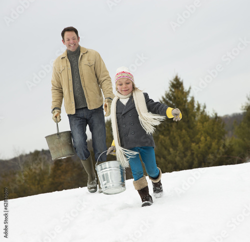 A man and child carrying buckets, running through the snow.