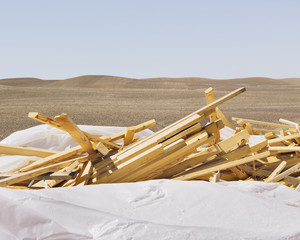 White tarp covering pile of wood 2x4 studs, farmland in background, near Pullman