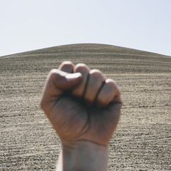 A hand bunched up and making fist, making a gesture. A ploughed field and farmland in the background, near Pullman in Washington state.