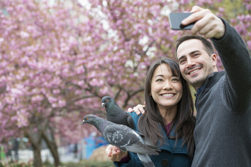 A couple, a man and woman, in the park, taking a selfy, self portrait with a mobile phone. Two pigeons perched on her wrist.
