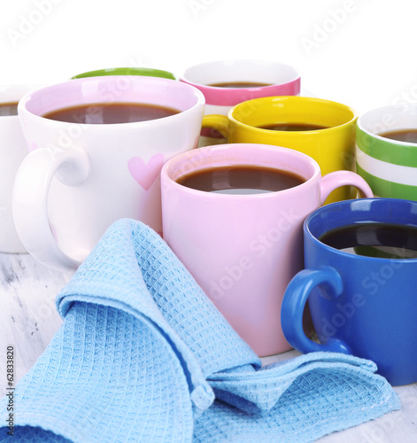 Many cups of coffee on wooden table isolated on white