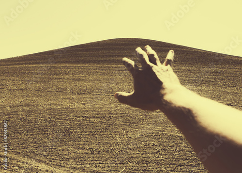 Hand extending towards ploughed farmland, near Pullman