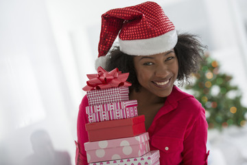 A woman wearing a red and white Father Christmas hat.  At home. A decorated Christmas tree.