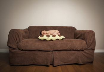 A naked newborn baby lying on his front, sleeping on a pillow on a brown couch.