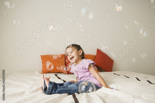 A young girl with brown eyes and dark hair in bunches sitting on a bed laughing. Bubbles floating in the air.