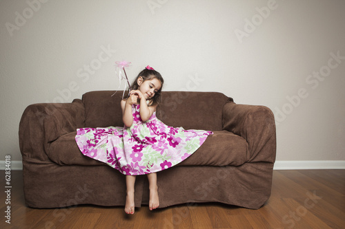 A 3 year old girl with long brown hair in a pink flowered cotton dress with the skirt spread out, waving a wand.