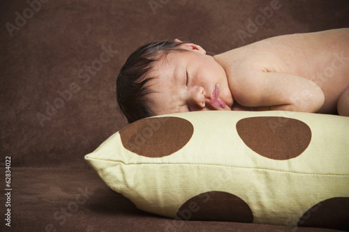 A newborn baby with his head turned to one side, lying sleeping on a polka dotted pillow.