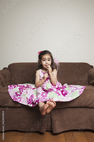 A 3 year old girl with long brown hair in a pink flowered cotton dress with the skirt spread out, sitting on a brown sofa.