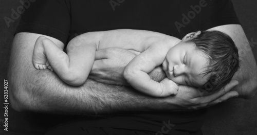 A naked newborn baby sleeping in his father's arms.