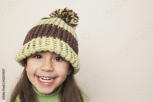 A young child with long brown hair, wearing a knitted hat with a pompom.