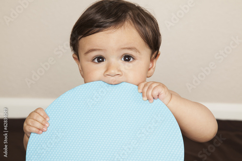 A young 8 month old baby boy wearing cloth diapers, holding a large blue disc and chewing the edge.