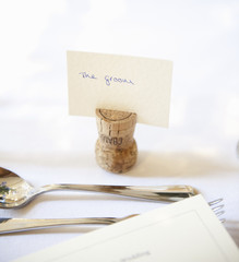 Close up of a place setting at the top table at a wedding banquet. An upside down cork with name tag for the groom. Silver fork and spoon.