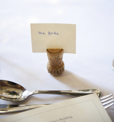 Close up of a place setting on the top table at a wedding banquet. An upside down cork with a name tag for the bride. Silver fork and spoon.