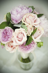 A bridal bouquet of pastel coloured pink roses, and pale lavender peonies with small green leaves.