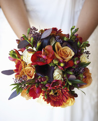 A bride holding a bridal bouquet of colourful red and orange flowers with purple toned leaves.