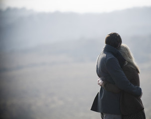 A couple embracing. Standing in a field in the country.