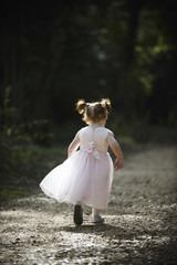A little girl, a bridesmaid in a pink dress running along a path.