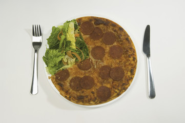 A salami pizza and salad on a plate.
