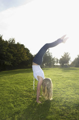 Teenage girl with long blond hair doing a headstand.