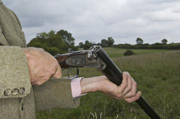 Man holding an open rifle.