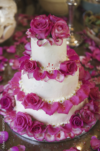 A three tiered wedding cake, covered in white frosting and decorated with pink rose petals.