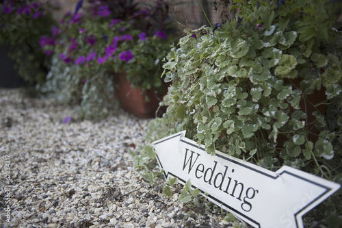 Directional sign to a wedding, on a gravel  path.