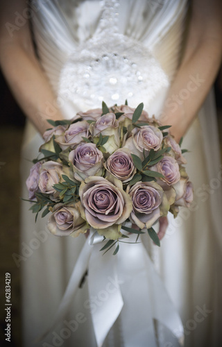 A bride in a white dress, holding a bridal bouquet of pastel coloured roses.