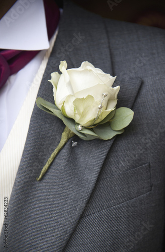 A groom in a grey jacket and white shirt, with a white rose boutonniere, in his buttonhole.