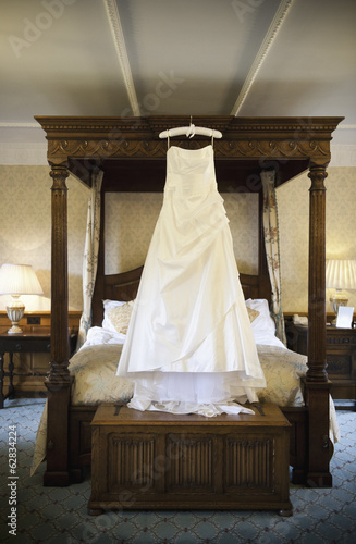 A full length white wedding dress hanging from a hanger on a four-poster bed.
