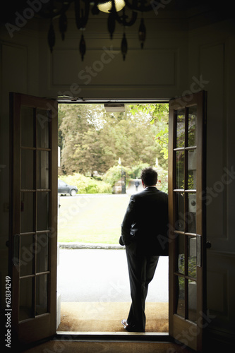 Silhouette of a man standing in a doorway leaning against the door frame, looking out into the garden.