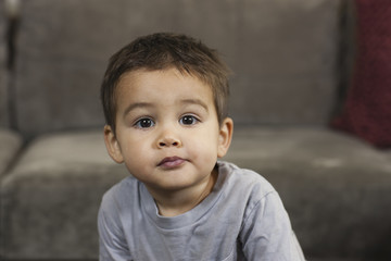 A young boy sitting looking at the camera with a serious expression.
